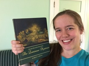 Karina Tabone holding up The Luminous Mysteries. Via IllustratedPrayer.com