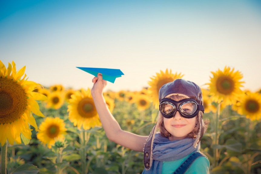Happy child playing with toy airplane against summer sky background. Travel and vacation concept. Retro toned