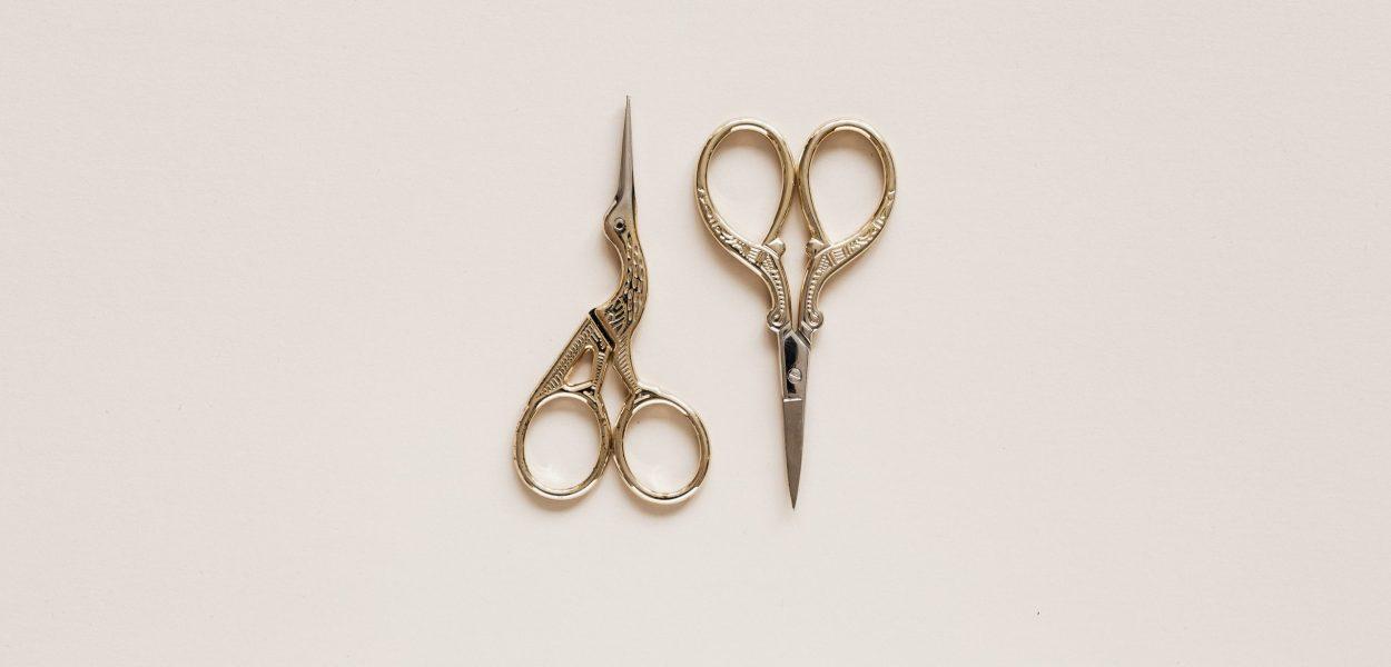 Small golden scissors on beige surface