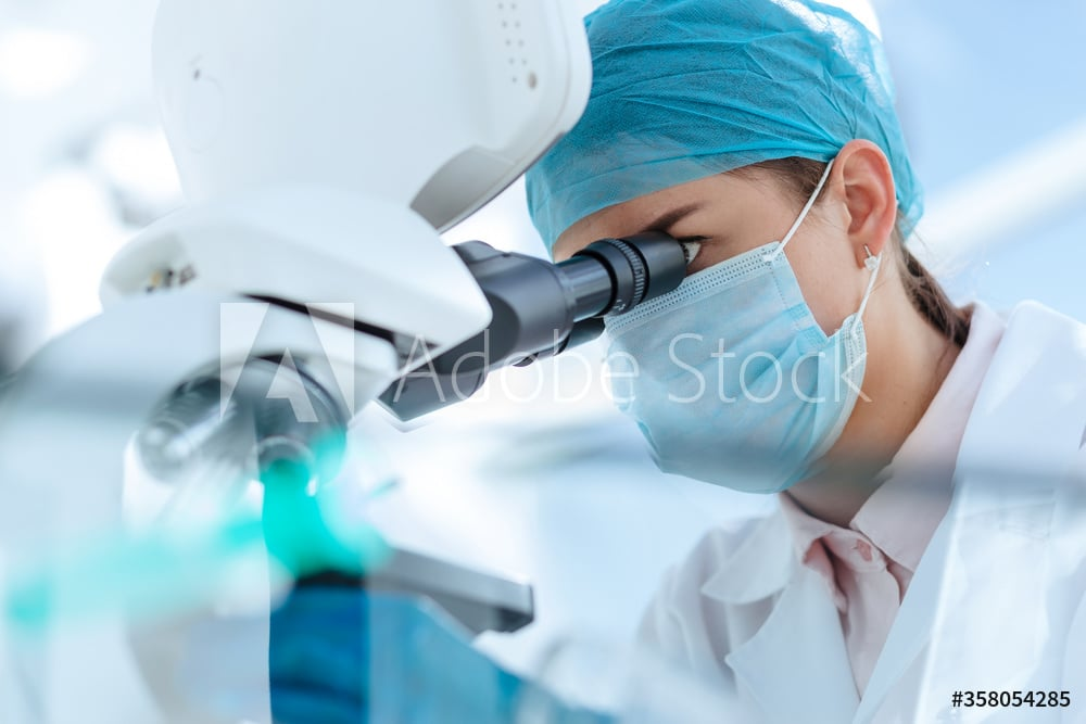 female scientist looking carefully through a microscope.