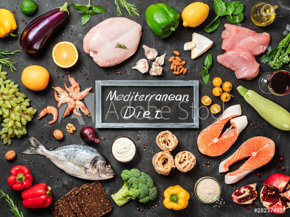 Mediterranean diet concept. Top view of food ingredients and chalkboard with words Mediterranean Diet in center. Dark background. Flat lay.