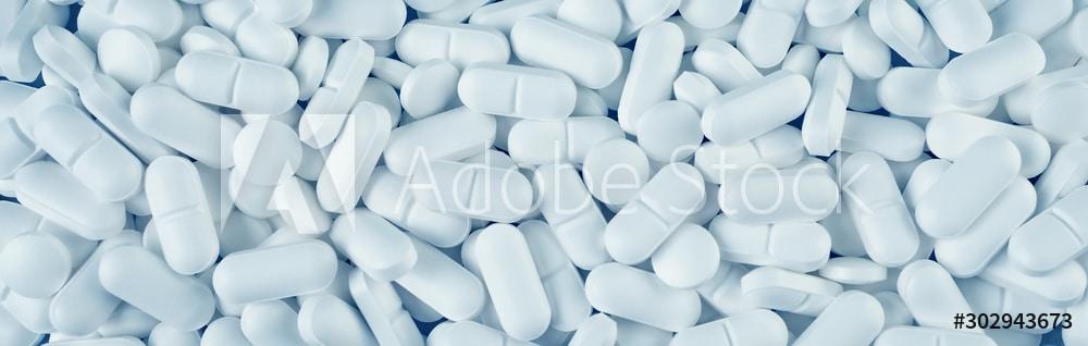 White pills spilled on blue wooden background