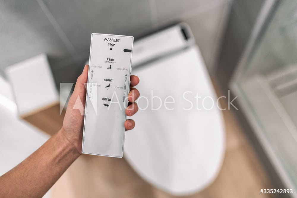 Smart japanese bidet automated toilet washlet with remote for easing cleaning rinsing with water without using toilet paper. at home bathroom modern lifestyle.