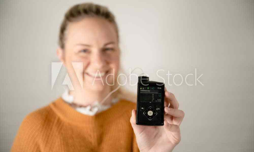 Attractive blonde woman holding her insulin pump - treating diabetes with technology