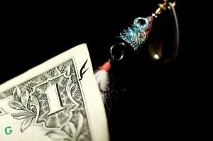 A fish hook snags a dollar bill.
