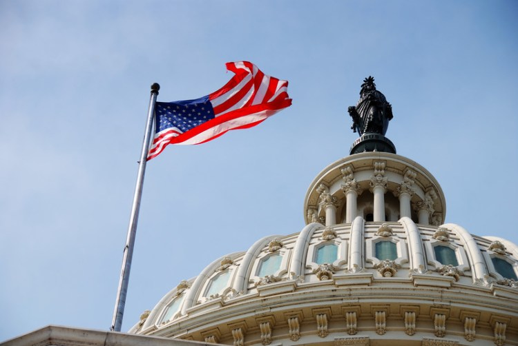 Artistic shot of the capitol dome and the American flag extended in the breeze.