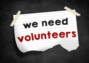 "A lined white paper is taped to a blackboard. It states, ""we need volunteers"""