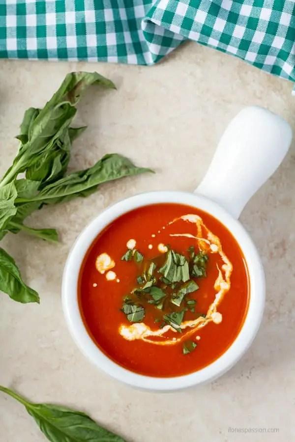Fresh basil around tomato soup.