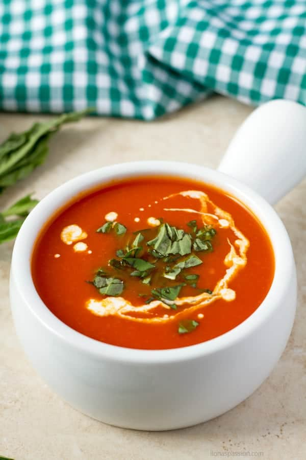 Freshly made soup with tomatoes topped with whipped cream.