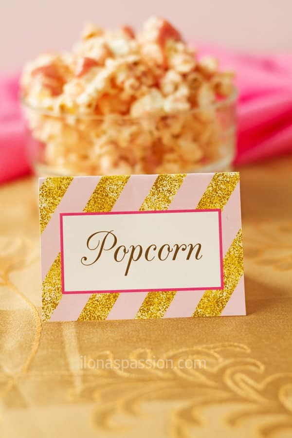 Pink and gold party decorations and ideas including table tent, popcorn with strawberry frosting.