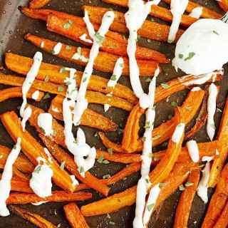 A close up phopto of cut lenghtwise carrot french fries and served with lemon dip.