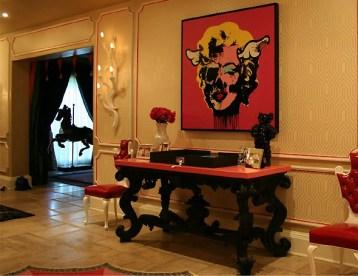 No detalhe do saguão principal, uma mesa com fotos pessoais serve de aparador ao lado da porta da sala de jantar