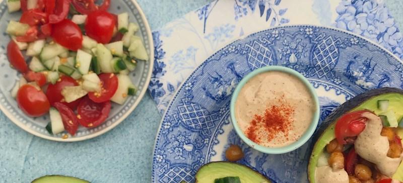 Gezonde vegetarische lunch: Gevulde avocado met geroosterde kikkererwten, komkommer, tomaat en romige tahinsaus