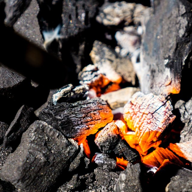 Lump charcoal glows with bright orange embers