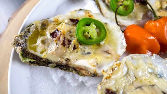 Grilled Oyster covered in butter, cheese, jalapeños sitting on a plate of salt.