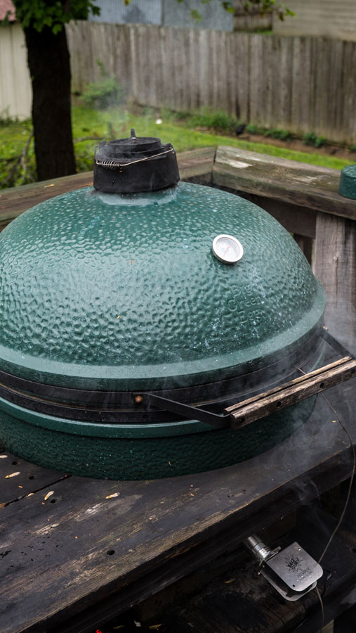 Big Green Egg with a BBQ guru attached smoking bacon.