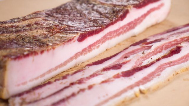 Thick slices of bacon laying on butcher paper.
