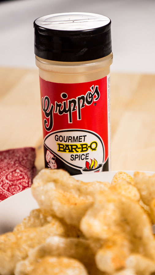 Can of Grippo's BBQ Seasoning behind a plate of pork rinds.