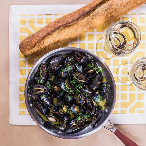 mussels in a skillet with crusty French bread and white wine.