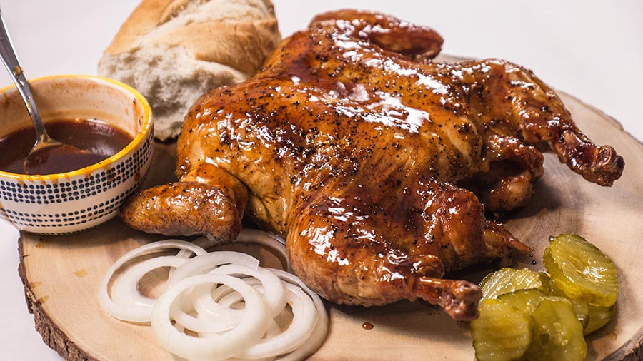cooked spatchcocked chicken with onions and pickles