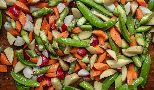 Diced Spring vegetables spread across a baking sheet.