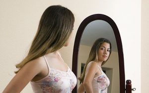 Teenage girl (14-15) looking in to mirror, side view