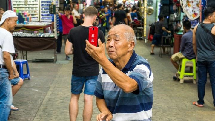 Un homme fait un selfie à Chinatown de Kuala Lumpur