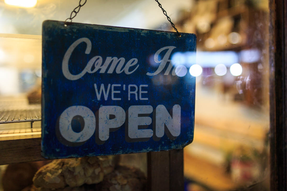 """Photo showing a slate hanging tile with white writing saying """"Come in We're Open"""""""