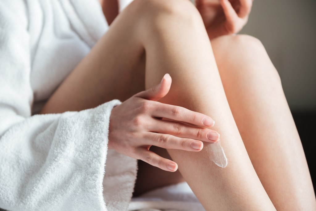 A photo of a woman applying lotion to her right leg