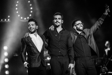 Left to right: Black and white photo of Gianluca, Ignazio and Piero with their arms around each other on stage