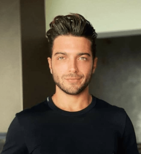 Gianluca in a black shirt looking at the camera