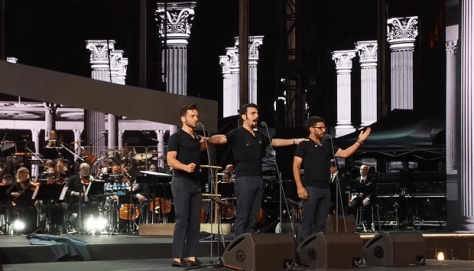 Left to right: Gianluca, Ignazio and Piero singing in casual attire on the arena stage