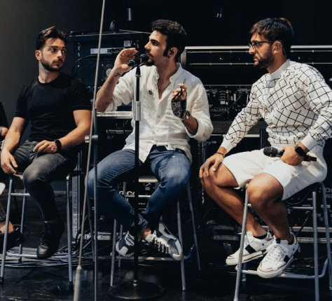 Left to right: Gianluca, Ignazion and Pieron sitting on stools rehearsing on the Ariston stage