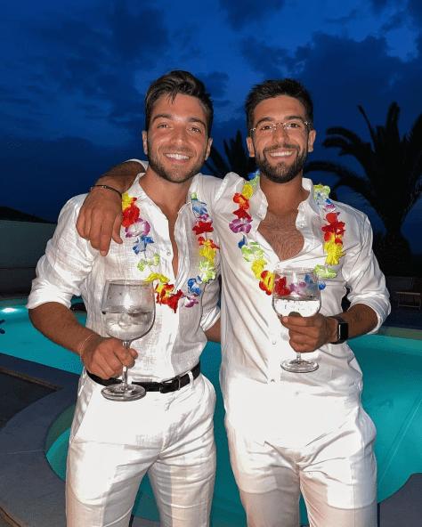Gianluca and PIero dress all in white with flower leis around their necks