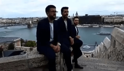 Left to right: Piero, Ignazio and Gianluca sitting on a wall with the river behind them