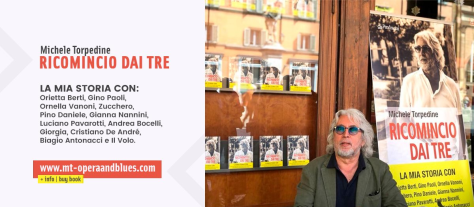 Michele Torpedine sitting in front of a display of the book he wrote
