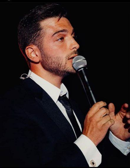 Gianluca holding a microphone singing
