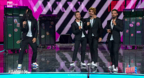 Cattelan on left with long black wig with Gianluca, Ignazio with gold wig and Piero all singing