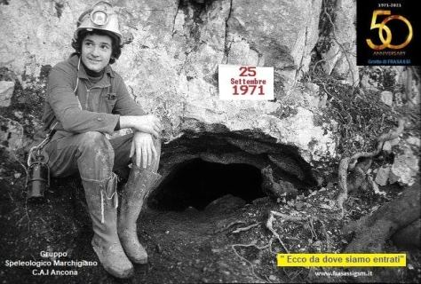 Black and white photo of a young cave explorer at the original entrance of the caves