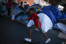A youth plays in a makeshift migrant camp near El Chaparral pedestrian border bridge in Tijuana, Mexico, Thursday, July 1, 2021…