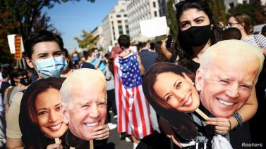 People hold cardboard cutouts after media announced that Democratic U.S. presidential nominee Joe Biden has won the election.