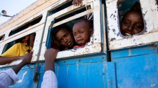 Refugees who fled the conflict in Ethiopia's Tigray region ride a bus going to the Village 8 temporary shelter, near the Sudan-Ethiopia border, in Hamdayet, eastern Sudan, Dec. 1, 2020.