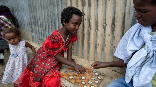 Elena, 7, left, plays a game of checkers using soda bottle tops with friend Hailemariam, 12, right, at a reception and day…