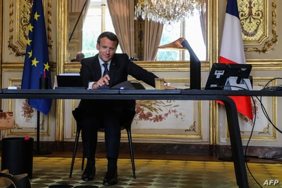 FILE - French President Emmanuel Macron conducts a phone call in his office at the Elysee Palace in Paris, France, on April 21, 2020.
