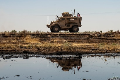 A US armoured vehicle drives past an oil field in the countryside of al-Qahtaniyah town in Syria's northeastern Hasakeh…