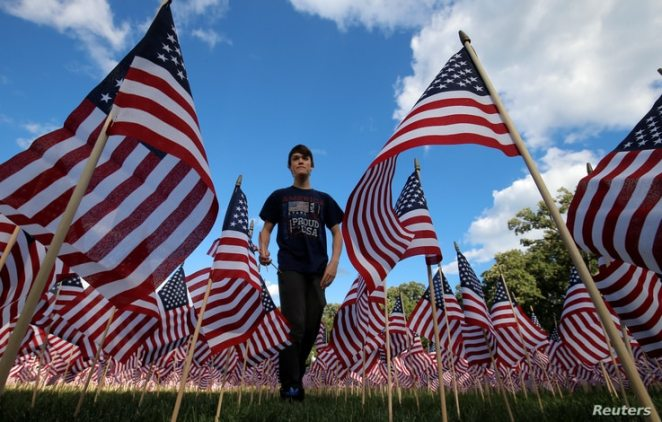 Jackson Tucker walks through the field  of 3,000 U.S. flags placed in memory of the lives lost in the September 11, 2001 attacks, at a park in Winnetka, Illinois, Sept. 10, 2016.