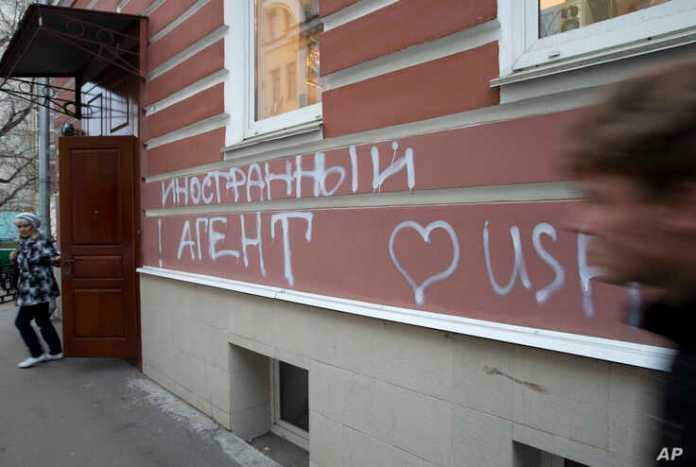 """FILE - A man walks past the office of """"Memorial"""" real group in Moscow, Russia.  The building has the words """"Foreign agent (loves) USA"""" spray-painted on its facade."""