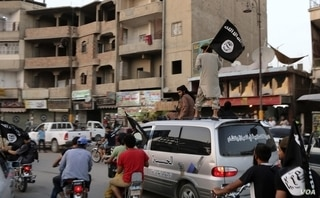 FILE - Members loyal to the Islamic State in Iraq and the Levant wave flags as they drive around Raqqa, June 29, 2014.