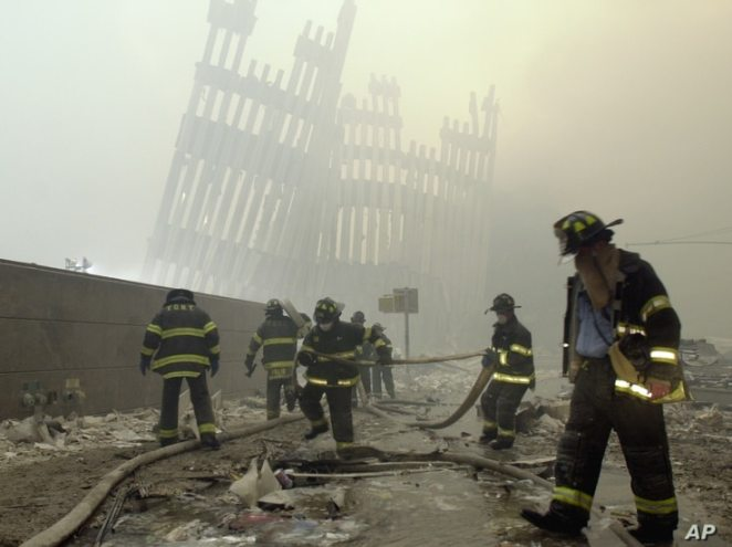 FILE - Firefighters work beneath the destroyed mullions, the vertical struts which once faced the soaring outer walls of the World Trade Center towers, after a terrorist attack on the twin towers in New York, Sept. 11, 2001.