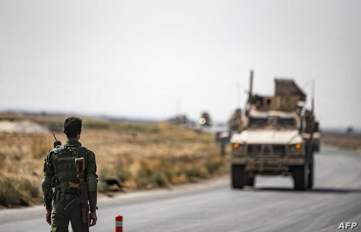 A fighter from the Syrian Democratic Forces SDF stands guard as a convoy of US military vehicles drives on a road after US…